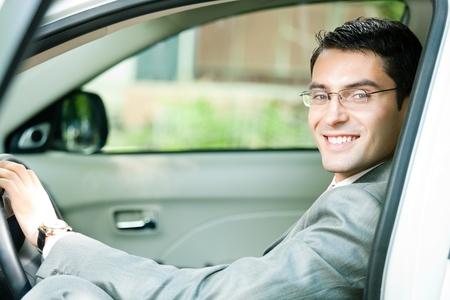 hombre conduciendo: Retrato de joven empresario sonriente feliz en el coche