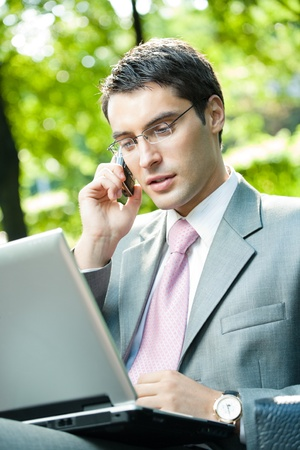 conference call: Young happy smiling business man working with laptop and cellphone, outdoors