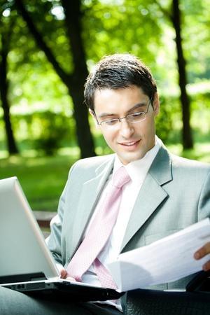 only men: Young happy smiling business man working with laptop, outdoors Stock Photo
