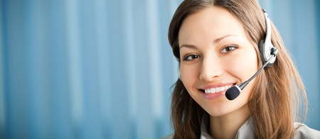 Portrait of happy smiling support phone operator in headset at workplace. To provide maximum quality, I have made this image by combination of two photos. You can use left part for slogan, big text or banner. photo