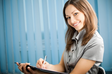 Portrait of writing happy smiling businesswoman working at office. You can use left part for slogan, big text or banner. Stock Photo - 10468114