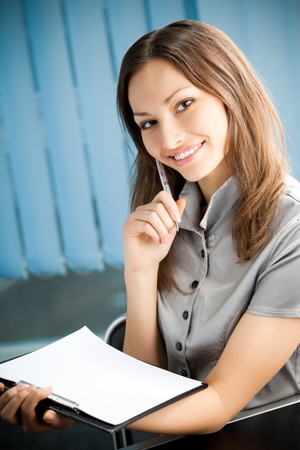 Portrait of writing happy smiling businesswoman working at office Stock Photo - 10468120