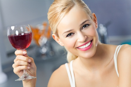 winetasting: Portrait of young woman with glass of red wine, at home