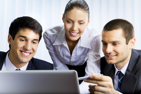 net meeting: Three happy smiling successful business people working with laptop at office Stock Photo