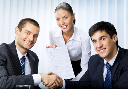 Three happy smiling successful business people handshaking with document at office  photo