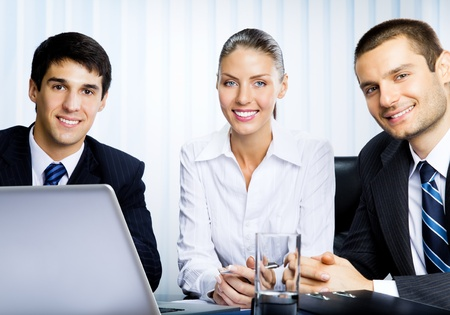 Portait of three happy smiling successful business people working with laptop at office