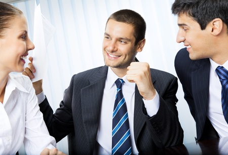 Happy smiling successful gesturing businessman with document and colleagues at office photo