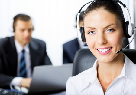 Portrait of happy smiling young female customer support phone operator in headset at office photo