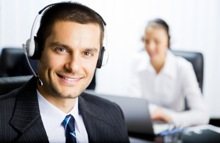 telephone headsets: Portrait of happy smiling customer support phone operator in headset at office