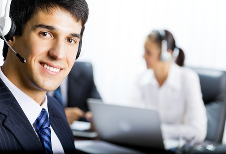 call center agent: Portrait of happy smiling customer support phone operator in headset at office