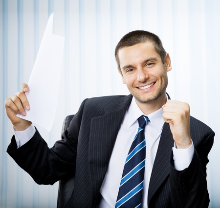 Happy smiling successful gesturing business man with document at office photo