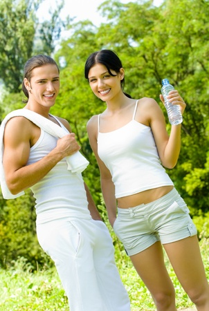 sport wear: Young happy smiling couple with bottle of water in sport wear on workout, outdoors Stock Photo