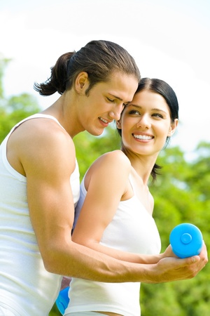 Young happy smiling couple in sport wear doing fitness exercise together, outdoors photo