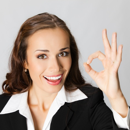 Happy smiling cheerful young business woman with okay gesture, over grey background photo
