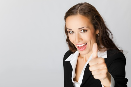 Happy smiling business woman showing thumbs up gesture, over grey background
