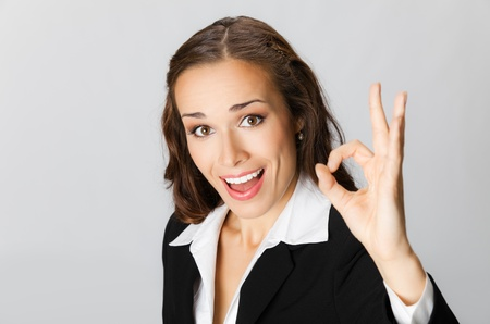 Happy smiling cheerful young business woman with okay gesture, over grey background Stock Photo - 10549082