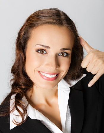 Young happy smiling business woman with call me gesture, over grey background photo
