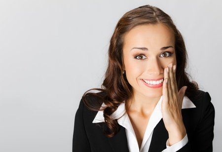 rumor: Portrait of happy smiling young business woman covering with hand her mouth, over grey background Stock Photo