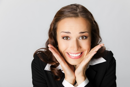 Portrait of young happy smiling surprised business woman, over grey background photo