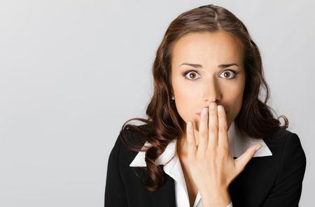 alzando la mano: Retrato de mujer sorprendida emocionada empresa joven con las manos cubriendo su boca, sobre fondo gris
