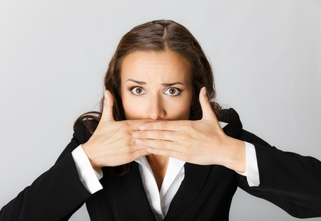 Portrait of surprised excited young business woman covering with hands her mouth, over grey background photo
