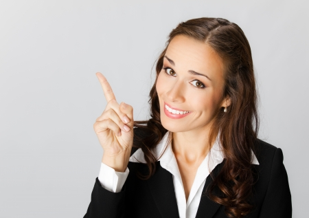 Happy smiling young business woman showing blank area for sign or copyspase, over grey background photo