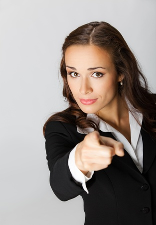 Portrait of young seus business woman pointing finger at viewer, over grey background Stock Photo - 10549096
