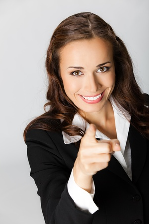 Portrait of young happy smiling business woman pointing finger at viewer (index finger gesture), over grey background photo