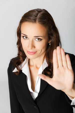 Serious young business woman showing stop gesture, over grey background Stock Photo - 10549105