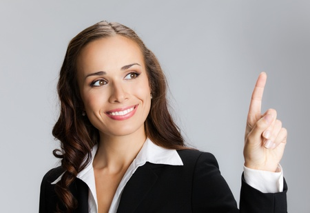 Happy smiling young business woman showing blank area for sign or copyspase, over grey background