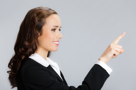 Happy smiling young business woman showing blank area for sign or copyspase, over grey background Stock Photo - 10549098