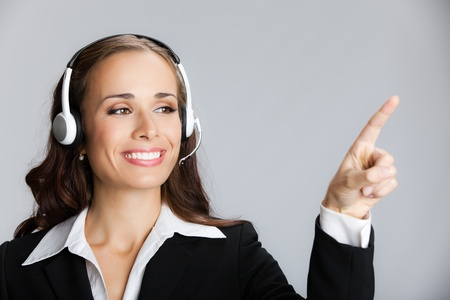 Portrait of happy smiling cheerful customer support phone operator in headset pointing at something, over grey background photo