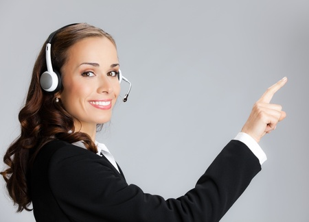 sales call: Portrait of happy smiling cheerful customer support phone operator in headset pointing at something, over grey background Stock Photo