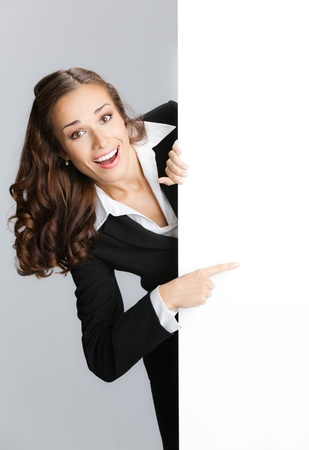 motto: Happy smiling young business woman showing blank signboard, over grey background