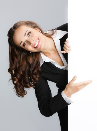 Happy smiling young business woman showing blank signboard, over grey background photo