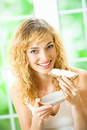 crispbread: Ritratto di giovane donna felice di mangiare fette biscottate con formaggio a casa propria
