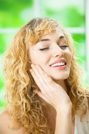Portrait of young beautiful smiling woman applying moisturizer cream on face, at home photo
