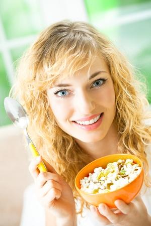 muslin: Young happy smiling beautiful woman eating muslin at home