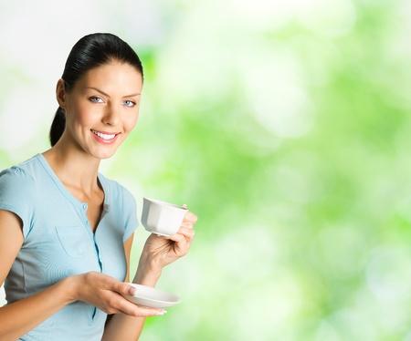 slogan: Joven mujer sonriente feliz tomando un caf�, al aire libre. Para proporcionar la m�xima calidad, he hecho esta imagen, por la combinaci�n de dos fotos. Puede utilizar parte derecha lema, texto grande o banner. Foto de archivo