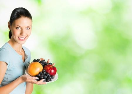 part of me: Joven mujer sonriente feliz con placa de frutas, al aire libre. Para proporcionar la m�xima calidad, he hecho esta imagen, por la combinaci�n de dos fotos. Puede utilizar parte derecha lema, texto grande o banner.