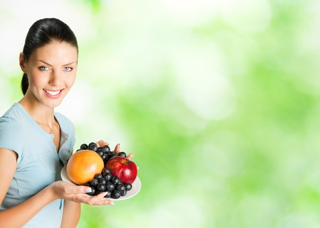 Young happy smiling woman with plate of fruits, outdoor. To provide maximum quality, I have made this image, by combination of two photos.You can use right part for slogan, big text or banner. Stock Photo - 10611703