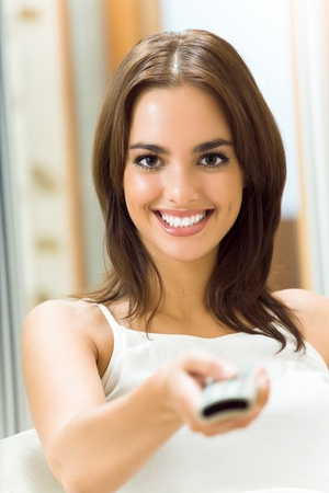 woman watching tv: Portrait of young happy smiling woman watching TV at home