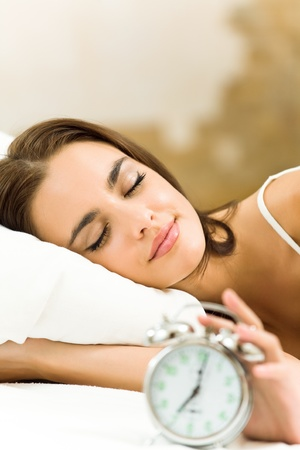 sleeping girl: Portrait of young beautiful woman with alarmclock lying on bed, at home