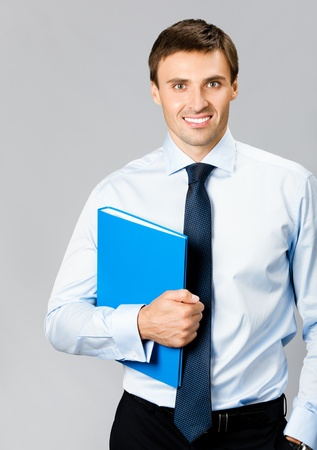 Portrait of happy smiling young business man with blue folder, over gray background photo