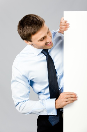 Portrait of happy smiling young business man showing blank signboard, over gray background photo