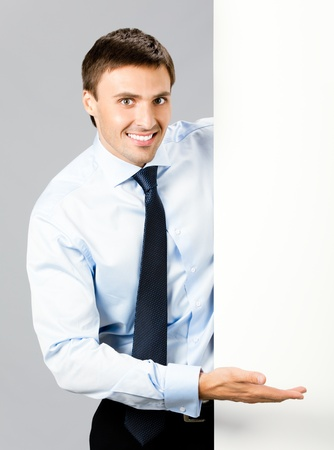 iş adamı: Portrait of happy smiling young business man showing blank signboard, over gray background