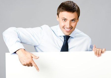 point of sale: Portrait of happy smiling young business man showing blank signboard, over gray background