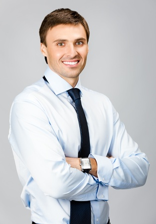 Portrait of happy smiling young business man, over gray background photo
