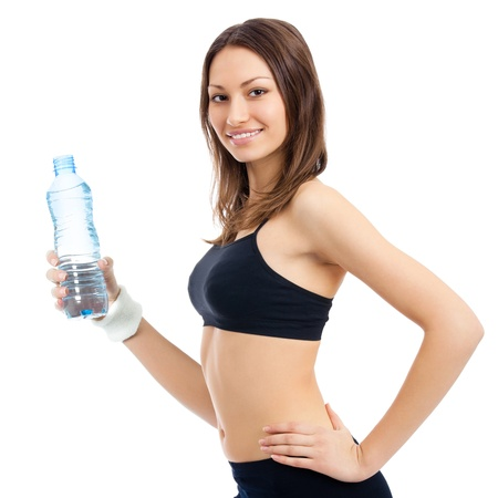 Portrait of happy smiling young woman in fitness wear with bottle of water, isolated over white background photo