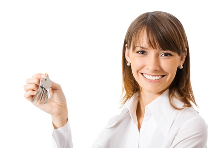 hand holding house: Young happy smiling business woman or real estate agent showing keys from new house, isolated on white background Stock Photo